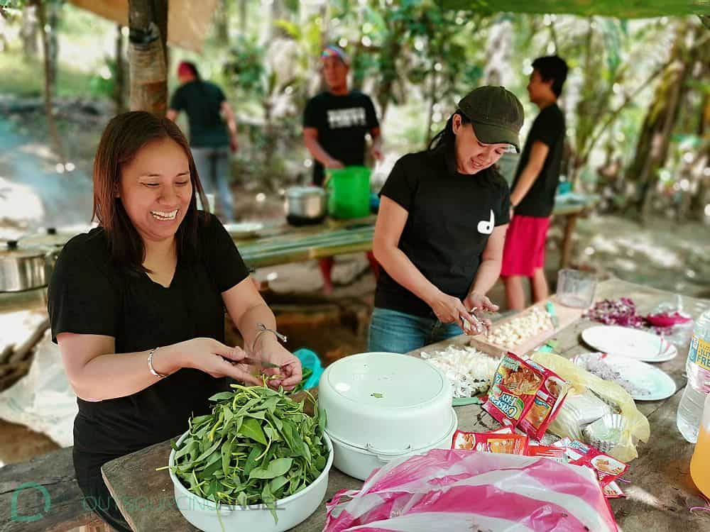 Outsourcing Angels sharing a lighthearted moment as they prepare food for the Dumagat Tribe